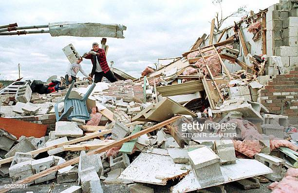 David Cottingham sifts through the remains of his father's Rock Creek, Alabama video store 09 April after a tornado ripped through the region 08...