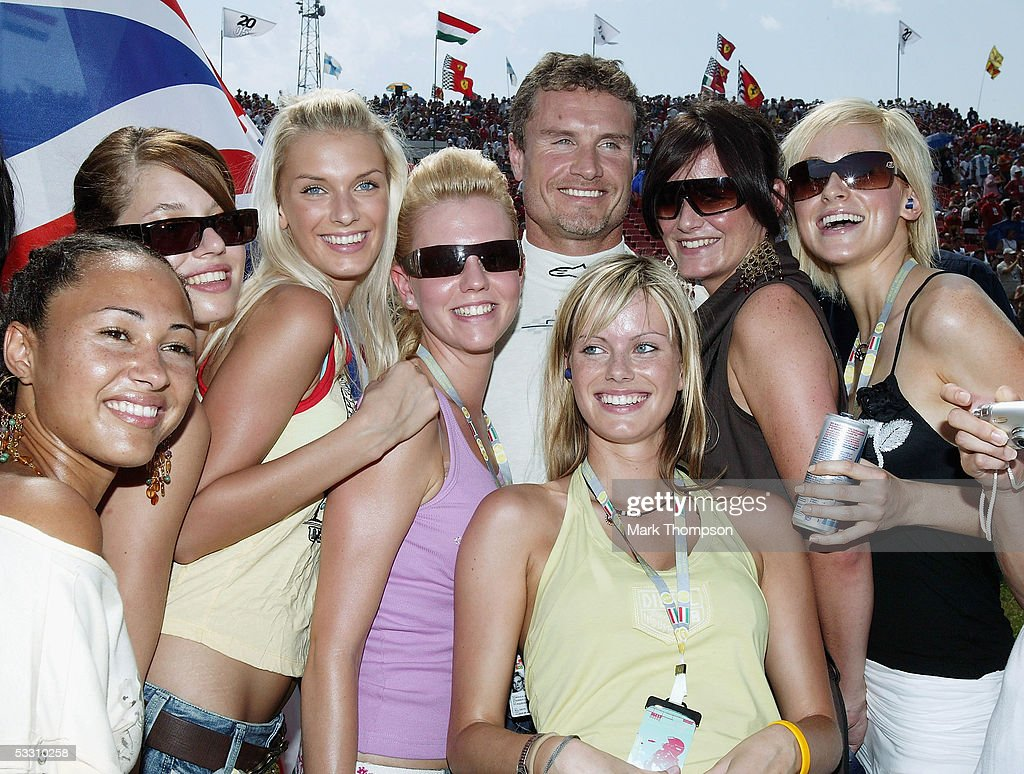 David Coulthard of Great Britain and Red Bull poses with F1 glamour girls on the grid during the Hungarian F1 Grand Prix at the Hungaroring on July 31, 2005 in Budapest, Hungary.