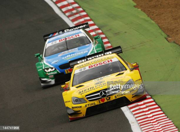 David Coulthard of Great Britain drives the DHL Paket Mercedes AMG C Coupe ahead of Augusto Farfus of Brazil in the Castrol Edge BMW M3 DTM during...