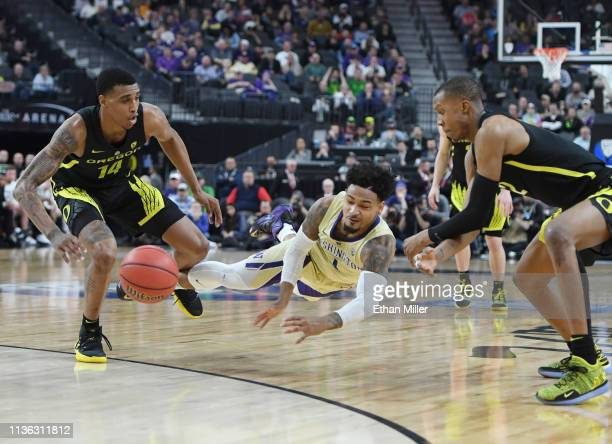 David Crisp of the Washington Huskies and Kenny Wooten and Louis King of the Oregon Ducks go after a loose ball during the championship game of the...