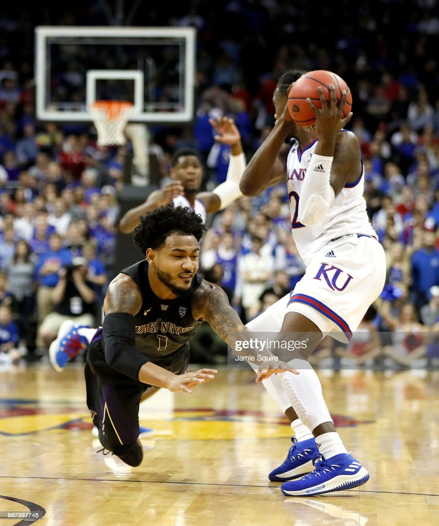 David Crisp #1 of the Washington Huskies dives for a loose ball as Lagerald Vick #2 of the Kansas Jayhawks scoops it up during the game at the Sprint Center on December 6, 2017 in Kansas City, Missouri.