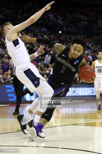 David Crisp of the Washington Huskies drives against Sam Merrill of the Utah State Aggies during the second half of the game in the first round of...