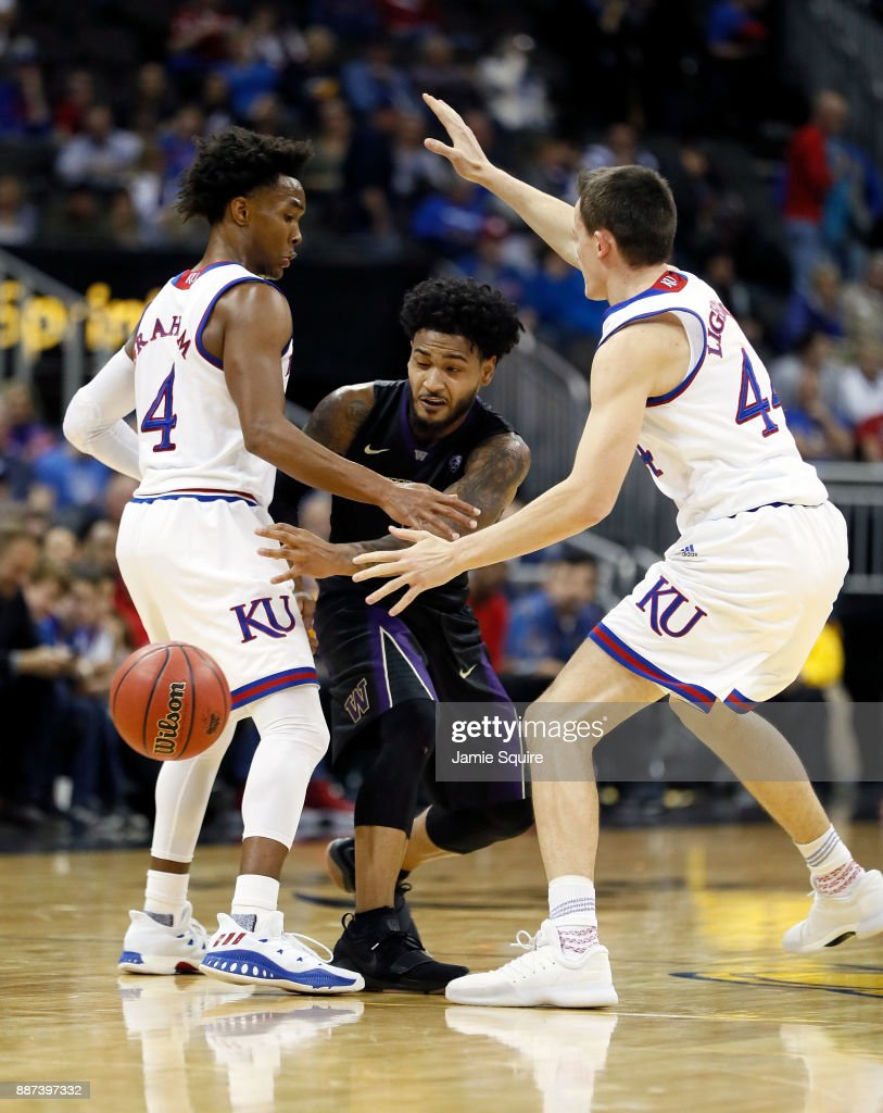 David Crisp #1 of the Washington Huskies passes the ball as Devonte' Graham #4 and Mitch Lightfoot #44 of the Kansas Jayhawks defend during the game at the Sprint Center on December 6, 2017 in Kansas City, Missouri.