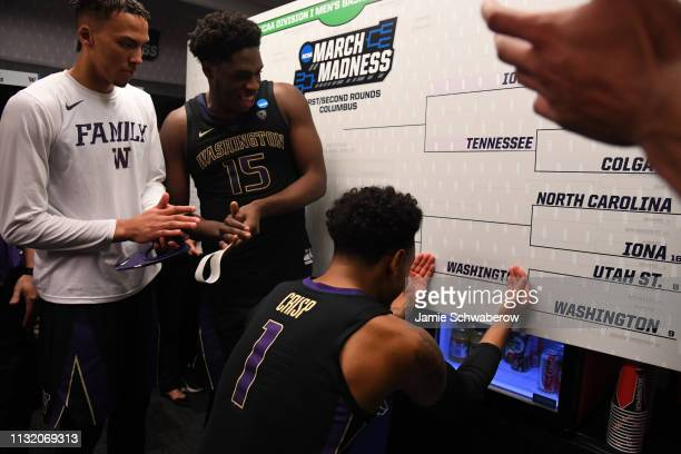 David Crisp of the Washington Huskies updates the locker room bracket after their win over the Utah State Aggies in the first round of the 2019 NCAA...