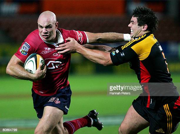 David Croft of the Reds fends off Ben May of the Chiefs during the round 11 Super 14 match between the Chiefs and the Queensland Reds at Waikato...