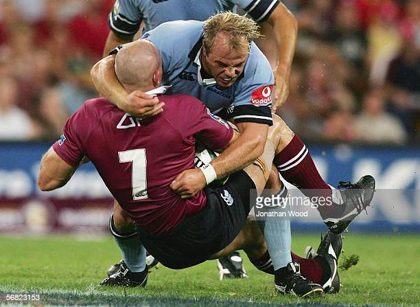 David Croft of the Reds is tackled by Phil Waugh of the Waratahs during the round one Super 14 match between the Queensland Reds and Waratahs at...
