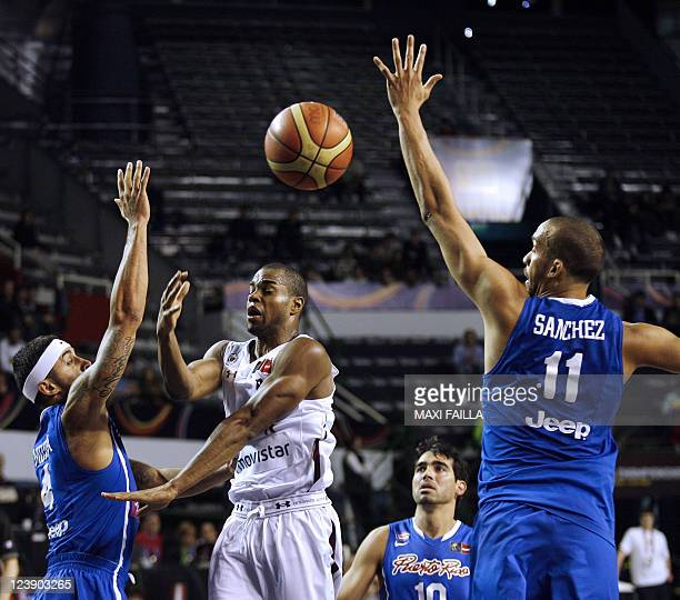 David Culliban of Venezuela vies with Javier Mojica and Ricardo Sanchez of Puerto Rico during the qualifying round of the 2011 FIBA Americas...