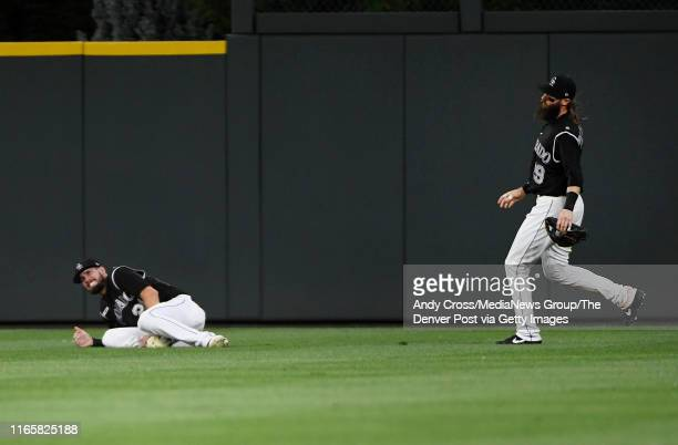 David Dahl grimaces in pain grabbing his right ankle as Colorado Rockies right fielder Charlie Blackmon runs toward him after went after a fly ball...