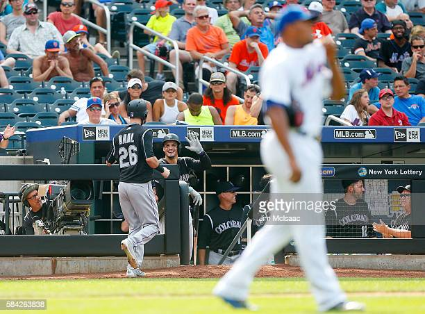 David Dahl of the Colorado Rockies celebrates with teammate Nolan Arenado after scoring a ninth inning run after a wild pitch from Jeurys Familia of...