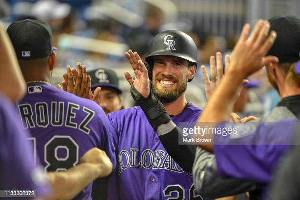 David Dahl of the Colorado Rockies celebrates with teammates in the dugout in the fifth inning against the Miami Marlins during Opening Day at...
