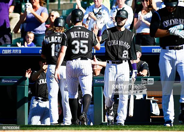 David Dahl of the Colorado Rockies congratulates Charlie Blackmon and Chad Bettis after they score on a base hit by Carlos Gonzalez in the bottom of...