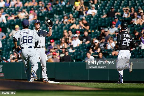 David Dahl of the Colorado Rockies hustles down the line as Jose Dominguez flips the ball to Wil Myers of the San Diego Padres during a regular...