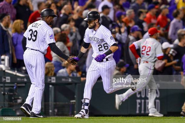 David Dahl of the Colorado Rockies is congratulated by third base coach Stu Cole as Gabe Kapler of the Philadelphia Phillies runs to check on...