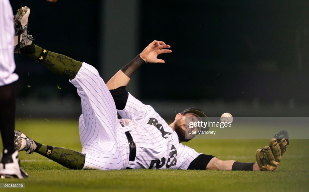 David Dahl #26 of the Colorado Rockies slides and misses a foul ball hit by Billy Hamilton #6 of the Cincinnati Reds in the ninth inning at Coors Field on May 26, 2018 in Denver, Colorado. Cincinnati won 6-5.