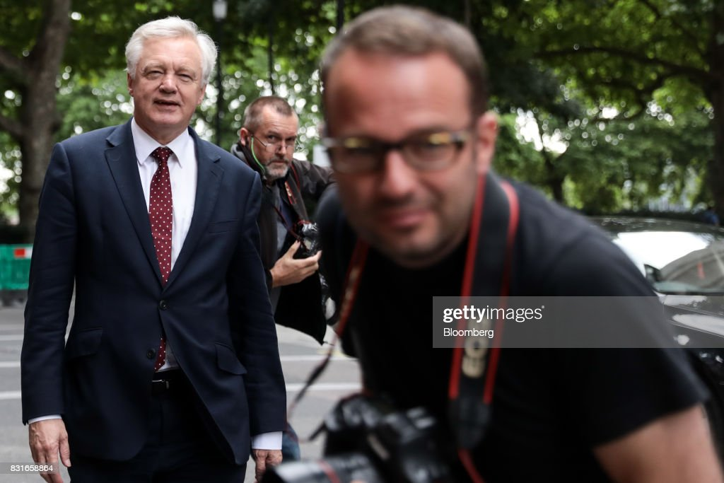 David Davis, U.K. exiting the European Union (EU) secretary, left, walks past photographers after doing a round of media interviews in London, U.K., on Tuesday, Aug. 15, 2017. The U.K. government said it wants to maintain tariff-free, bureaucracy-light trade with the European Union for a period of up to two years after Brexit, a proposalcheered by British businesses but which is likely to raise eyebrows on the continent. Photographer: Simon Dawson/Bloomberg via Getty Images