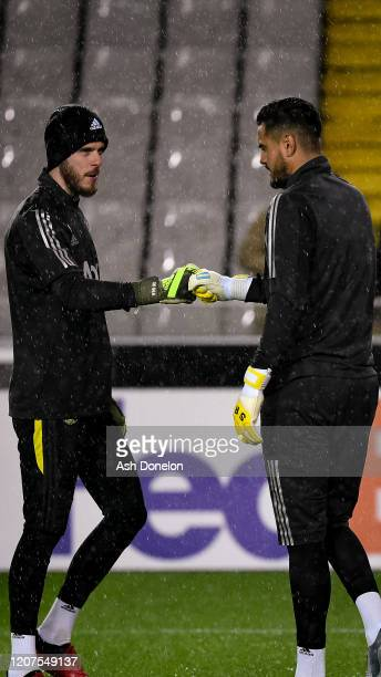 David de Gea and Sergio Romero of Manchester United warm up ahead of the UEFA Europa League Round of 32 first leg match between Club Brugge and...