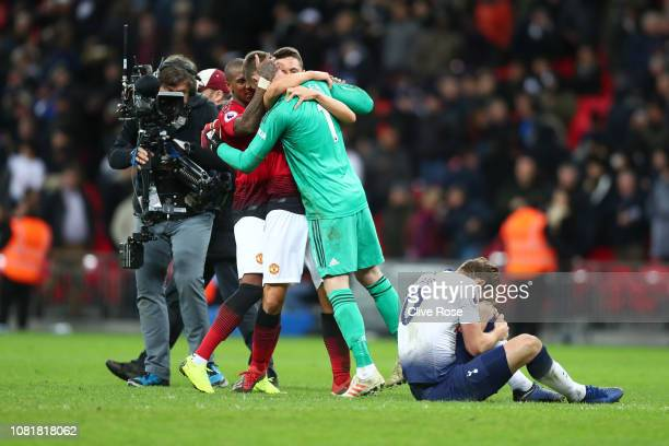 David De Gea of Manchester United celebrates with team mates following their sides victory as Harry Kane of Tottenham Hotspur is injured during the...