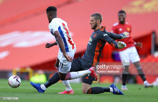 David De Gea of Manchester United is challenged by Wilfried Zaha of Crystal Palace during the Premier League match between Manchester United and...