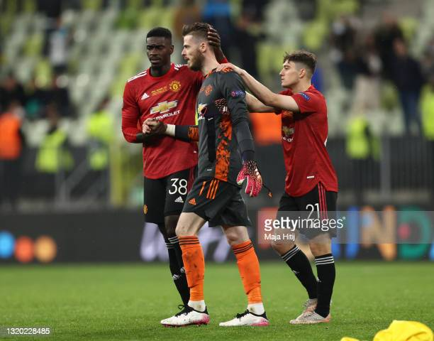 David De Gea of Manchester United is consoled by teammates Axel Tuanzebe and Daniel James following their team's defeat in the penalty shoot out...