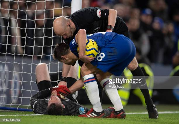 David de Gea of Manchester United lies injured as referee Anthony Taylor and César Azpilicueta of Chelsea help during the Premier League match...