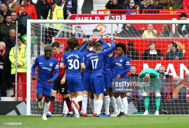 David De Gea of Manchester United looks dejected as Marcos Alonso of Chelsea celebrates scoring their first goal with team mates during the Premier...