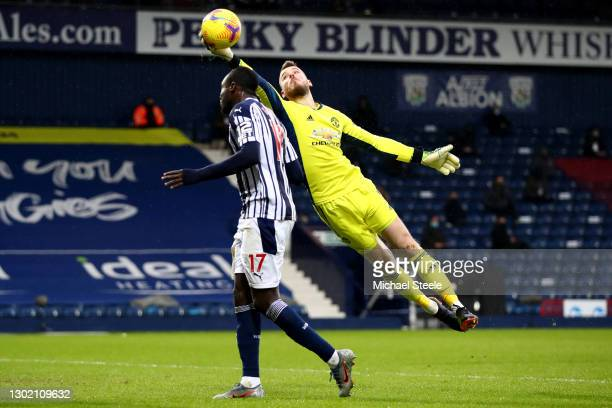 David de Gea of Manchester United makes a save from the head of Mbaye Diagne of West Bromwich Albion during the Premier League match between West...