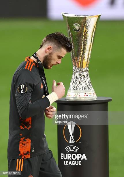 David De Gea of Manchester United removes their medal as they make their way past the UEFA Europa League Trophy following the UEFA Europa League...