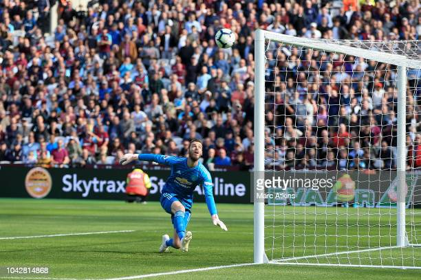 David De Gea of Manchester United watches the ball as a shot by Andriy Yarmolenko of West Ham United is deflected into the net for the second West...