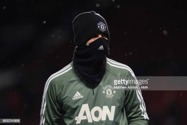 David de Gea of Manchester United wears a hat and snood in the cold weather whilst warming up during the FA Cup Quarter Final match between...