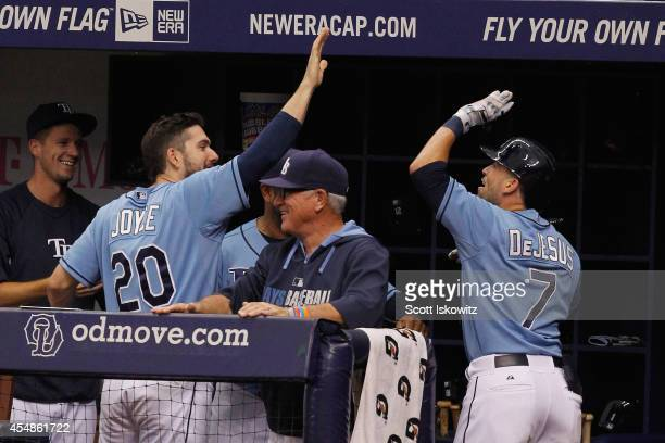 David DeJesus of the Tampa Bay Rays celebrates his insidethepark home run with teammate Matt Joyce and Joe Maddon during the fourth inning against...