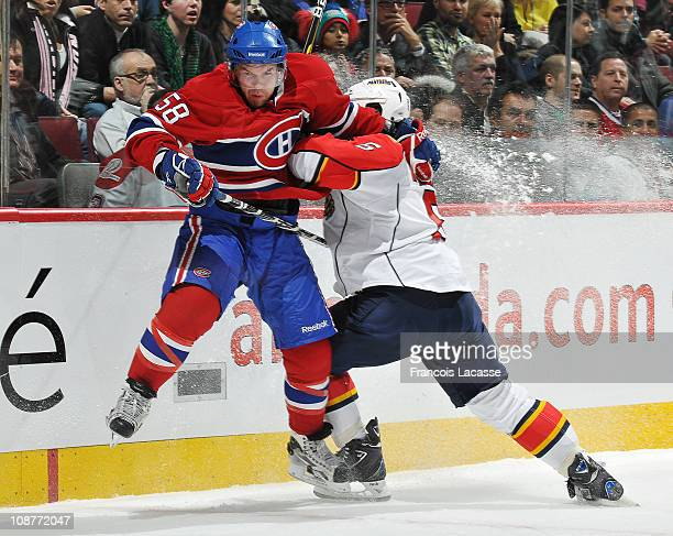 David Deshamais of the Montreal Canadiens is checked into the boards by Dennis Wileman of the Florida Panthers during the NHL game on February 2,...