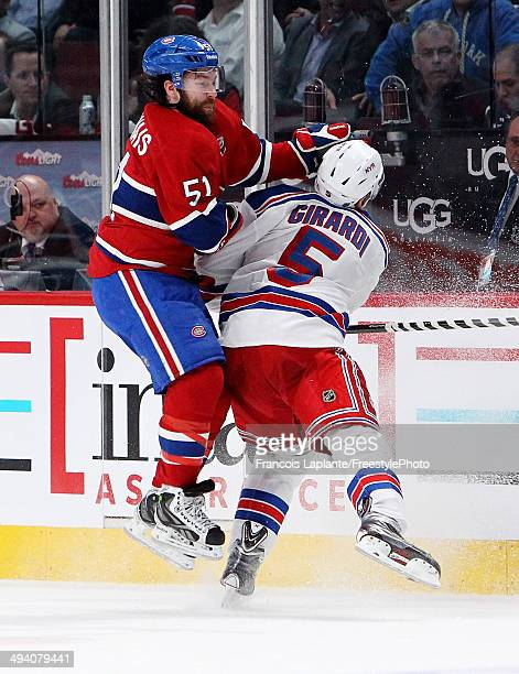 David Desharnais of the Montreal Canadiens and Dan Girardi of the New York Rangers collide along the baords during Game Five of the Eastern...
