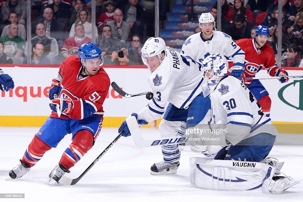 David Desharnais #51 of the Montreal Canadiens and Dion Phaneuf #3 of the Toronto Maple Leafs watch the loose puck in front of Ben Scrivens #30 during the NHL game at the Bell Centre on January 19, 2013 in Montreal, Quebec, Canada.
