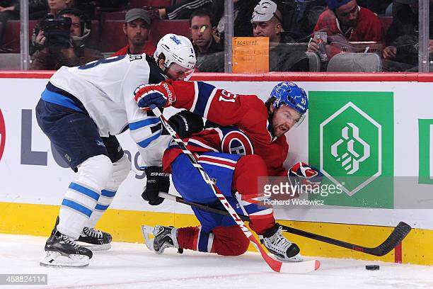 David Desharnais of the Montreal Canadiens and Jacob Trouba of the Winnipeg Jets battle for the puck during the NHL game at the Bell Centre on...