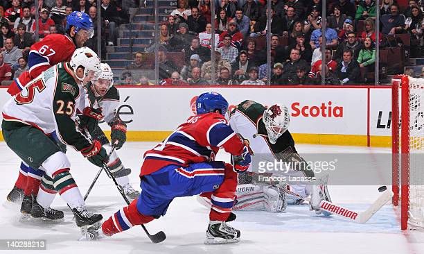 David Desharnais of the Montreal Canadiens deflects a pass from Max Pacioretty behind goaltender Josh Harding of the Minnesota Wild during the NHL...