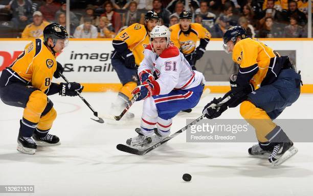 David Desharnais of the Montreal Canadiens passes the puck between Patric Horqnvist and Kevin Klein of the Nashville Predators at the Bridgestone...