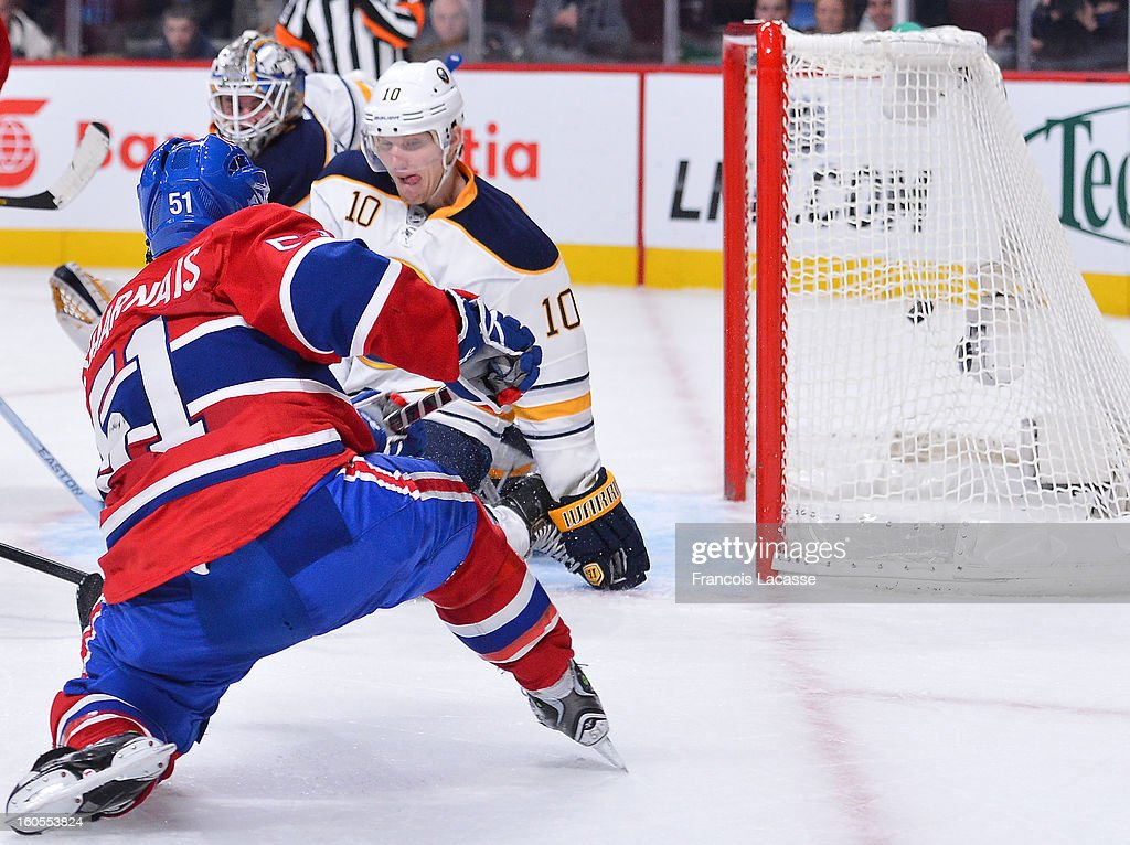 David Desharnais #51 of the Montreal Canadiens scores a goal despite Christian Ehrhoff #10 of the Buffalo Sabres kneeling in front of him during the NHL game on February 2, 2013 at the Bell Centre in Montreal, Quebec, Canada.