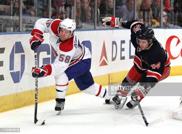 David Desharnais of the Montreal Canadiens skates with the puck as Steve Eminger of the New York Rangers defends during their game on March 18 2011...
