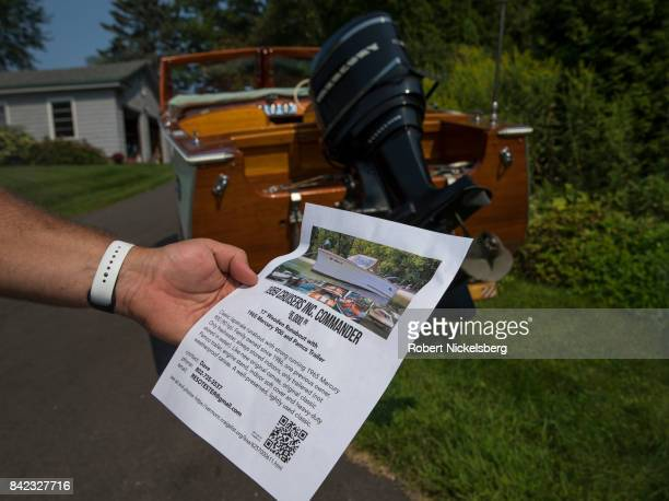David Desmet holds a for sale advertisement for his 1959 Cruisers Commander 17' wooden boat August 21 2017 in Charlotte Vermont The classic boat with...