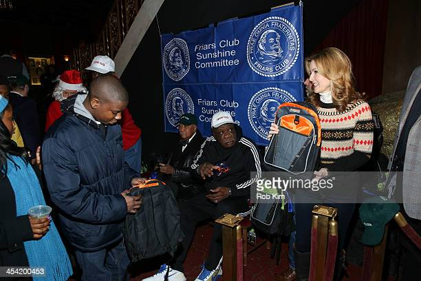 David Dinkins Cal Ramsey and Jodi Applegate hand out free bags to kids at the Cloudy With A Chance of Meatballs 2 Holiday Screening hosted by The...
