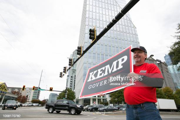 David Dollar waves a Kemp campaign sign at the corner of Piedmont Road and Peachtree Road on November 6 2018 in Atlanta Georgia Voters in Georgia are...