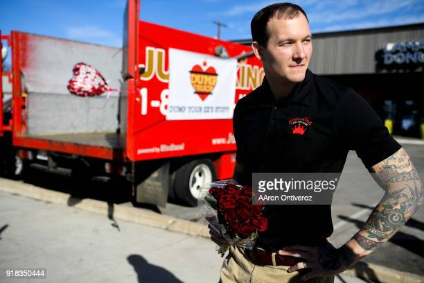 David Donovan of Junk King waits with a bouquet of roses for people to show up near the corner of Evans and Broadway to dump their Valentine's Day...