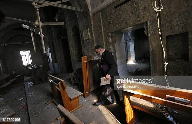 David Dosha, the priest of the Church of Mart Shmony, located in the Christian Iraqi town of Bartella, about 15 kilometres east of Mosul, inspects...