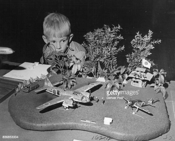 David Downing of 915 S Steels St Peers through Foliage at World War II Diorama The Pacific Island Japanese airbase was one of three dioramas entered...