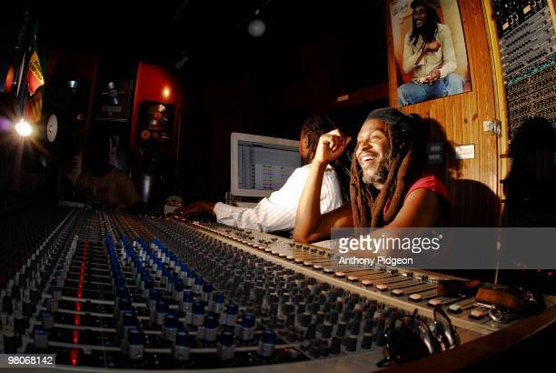 David 'Dread' Hinds of Steel Pulse sits behind the mixing desk in a studio control room while sound engineer Alrick Thompson uses computer recording...