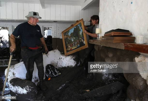 David Drenic and Robert Drenic look for salvageable items in a the home of a family member that was destroyed by a mudslide on January 11 2018 in...