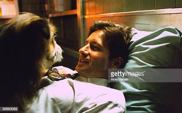 David Duchovny costar of cult TV series The XFiles lying on bed w pet dog on the set of the show