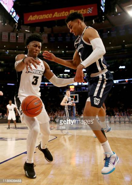 David Duke of the Providence Friars and Jordan Tucker of the Butler Bulldogs fight for the bal during the first round of the Big East Tournament at...