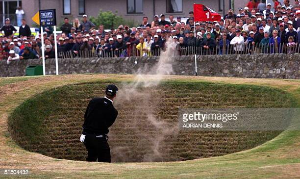 David Duval of the US hits out of the bunker on one of his three attempts to get onto the17th green from the hazard on the Old Course at St. Andrews...