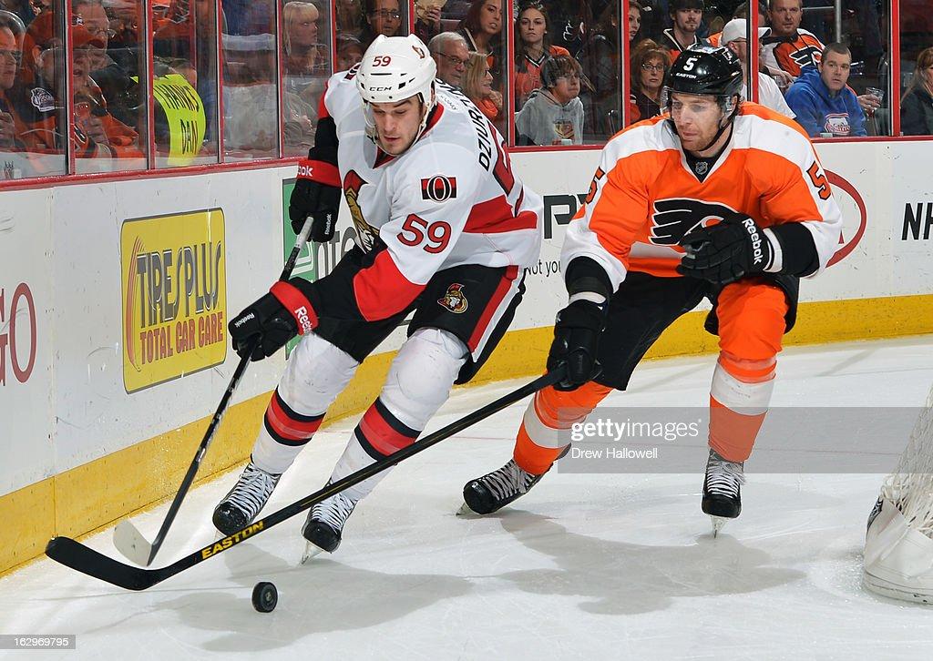 David Dziurzynski #59 of the Ottawa Senators and Braydon Coburn #5 of the Philadelphia Flyers skate for the puck at the Wells Fargo Center on March 2, 2013 in Philadelphia, Pennsylvania.